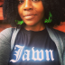 """headshot of Prof. Krystal Strong wearing a black shirt with white text that reads """"Jawn""""."""