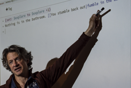 Instructor pointing a marker at a projected image of code on a screen