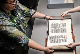 Dot porter works with staff to inspect a manuscript at the Penn libraries