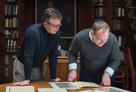Two men looking at texts laid out on a wooden table in a library reading room